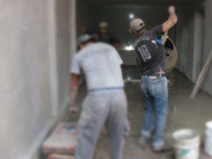 imagen de albañil colando piso de concreto